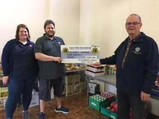 HELPING: Louise and John Melia, representing the Street Foodbank, being presented with a cheque by Lion David Atkins, of Glastonbury and Street Lions Club (CIO)