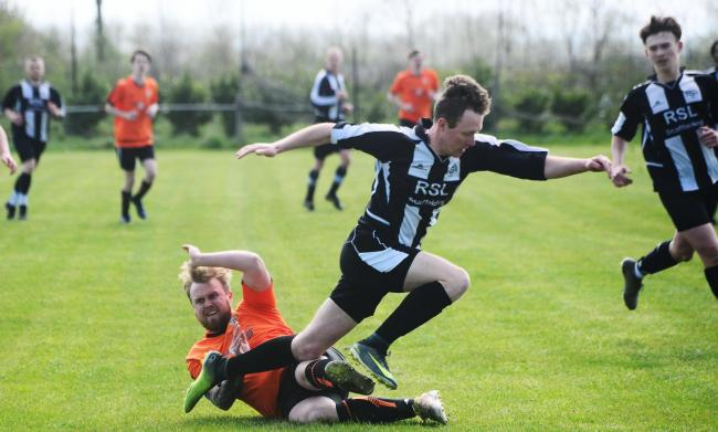 TACKLE: Middlezoy Rovers Athletic player Aaron Bown (black/white kit) and Nether Stowey's Zach Bryant (orange) (pic: Steve Richardson)