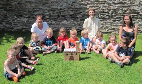 Christine Stevens, owner and manager of the nursery, Reverend Jane Haslam with staff members and some of the children.