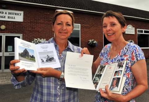 Maria Maye and Kate Symonds outside Moorland Village Hall with the recipe book and a letter of royal approval from the Queen.