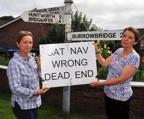 Villagers Maria Maye and Kate Symonds warn drivers not to follow their sat navs in Northmoor Green. Photo: Jeff Searle