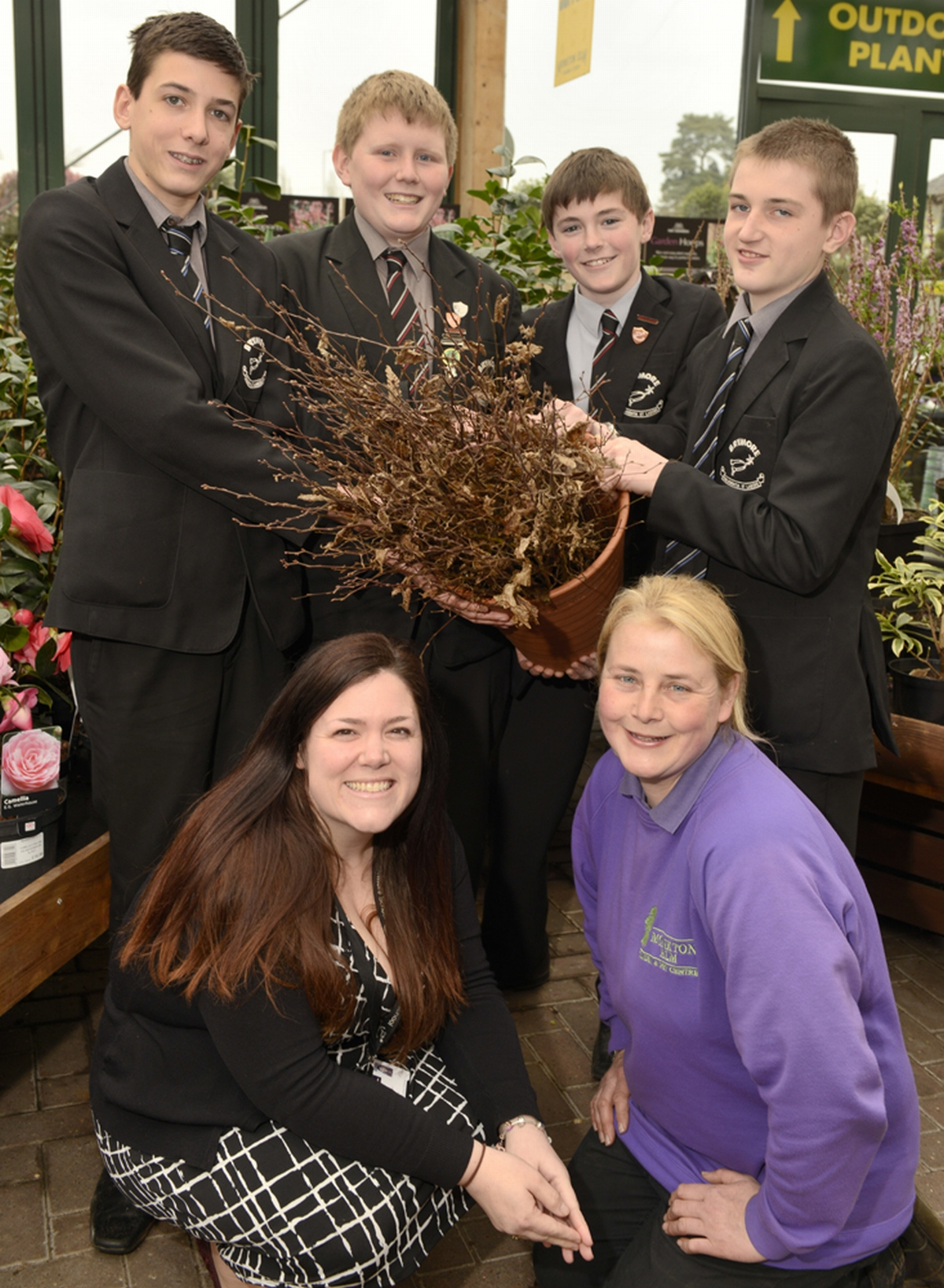 (Bottom left) Lorraine Warren, marketing manager at Brymore School and (top left to right) Ben Harris, 14, Charles Coleman, 15, Will Waind, 14, and Henry Phillips, 15, collect their saplings from (bottom right) Fiona Smart, head of plants.