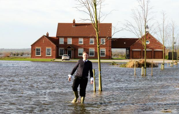 Sam Notaro wading through the moat around his house in his wellies to reach our photographer.
