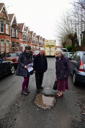Anne Heritage, Roy Franklin and Sue Blackmore stand by their street's giant pothole.