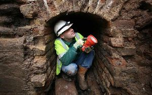 A worker crouches in the smugglers tunnel - which archaeologists suggest was used to move goods around into house in the town