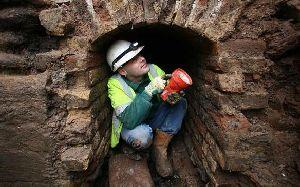 Bridgwater Mercury: A worker crouches in the smugglers tunnel - which archaeologists suggest was used to move goods around into house in the town