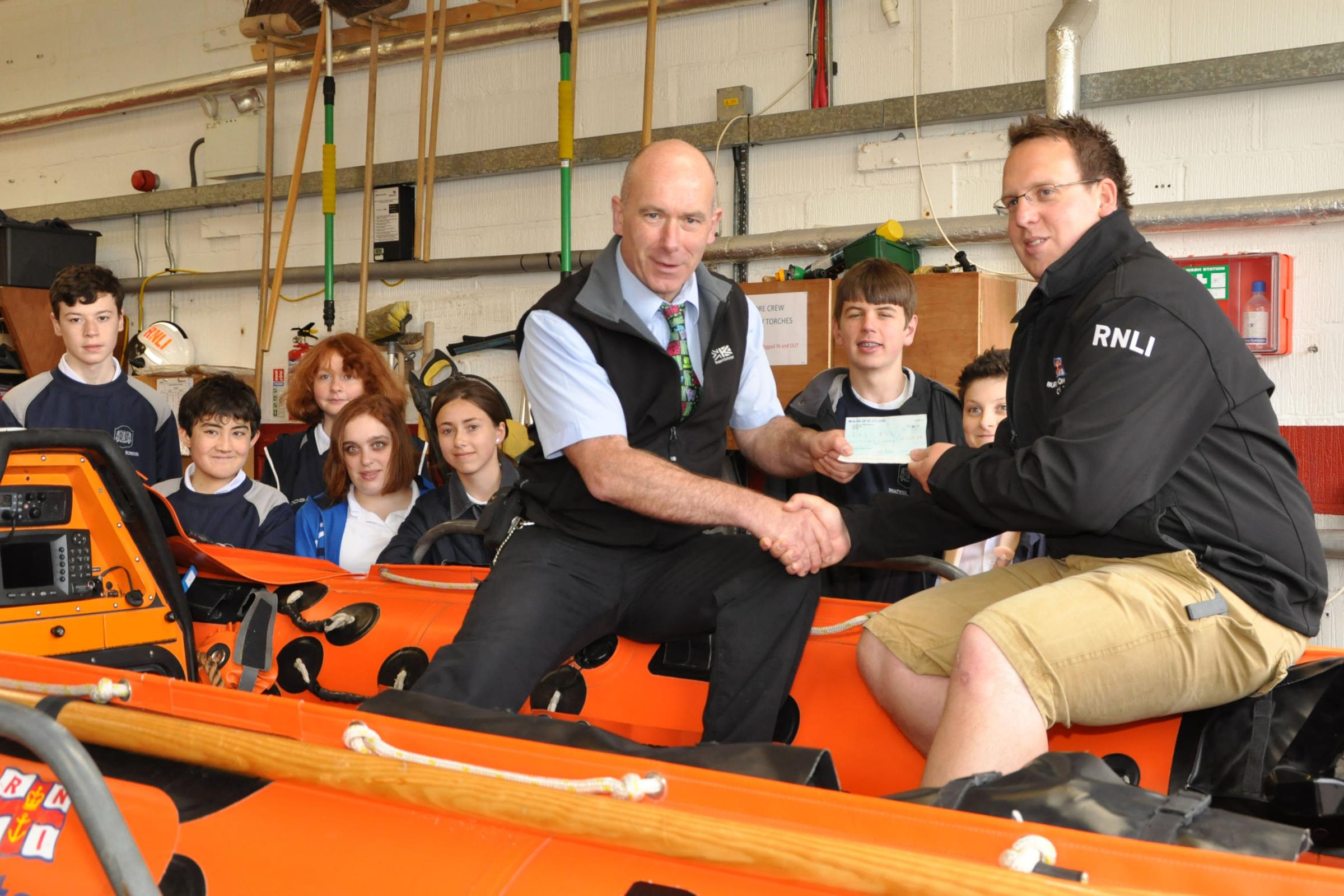 Dan Burnett hands the cheque for £1,002 to volunteer crew member Tim Walters