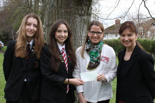 Imogen Keates and Phoebe Lane presenting Mrs Hancock with the cheque accompanied by head teacher Karen Canham.