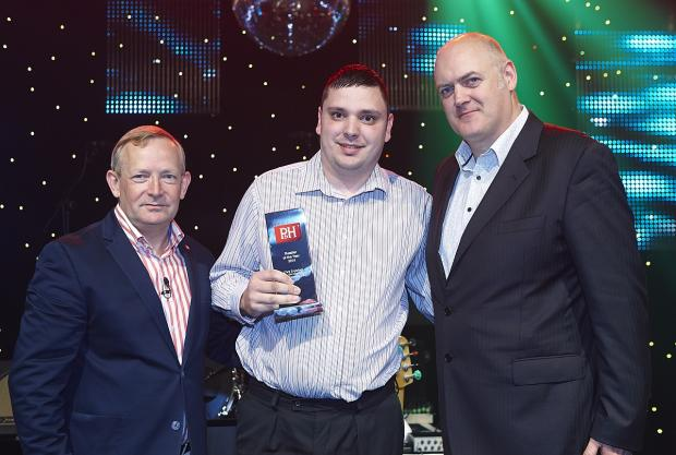 Chris Englefield, centre, receives his award from Palmer and Harvey managing director Martyn Ward, left, and comedian Dara Ó Briain, right.