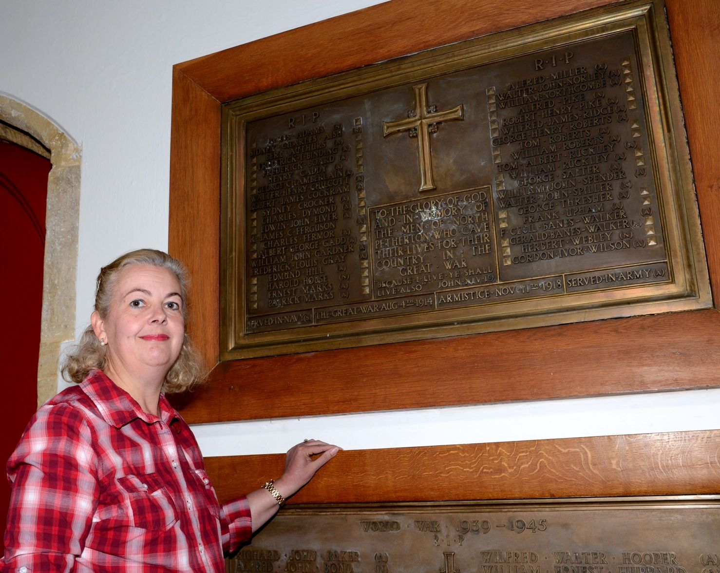 Wendy Mclean stands beside the war memorial plaque at North Petherton's Sty Mary's Church