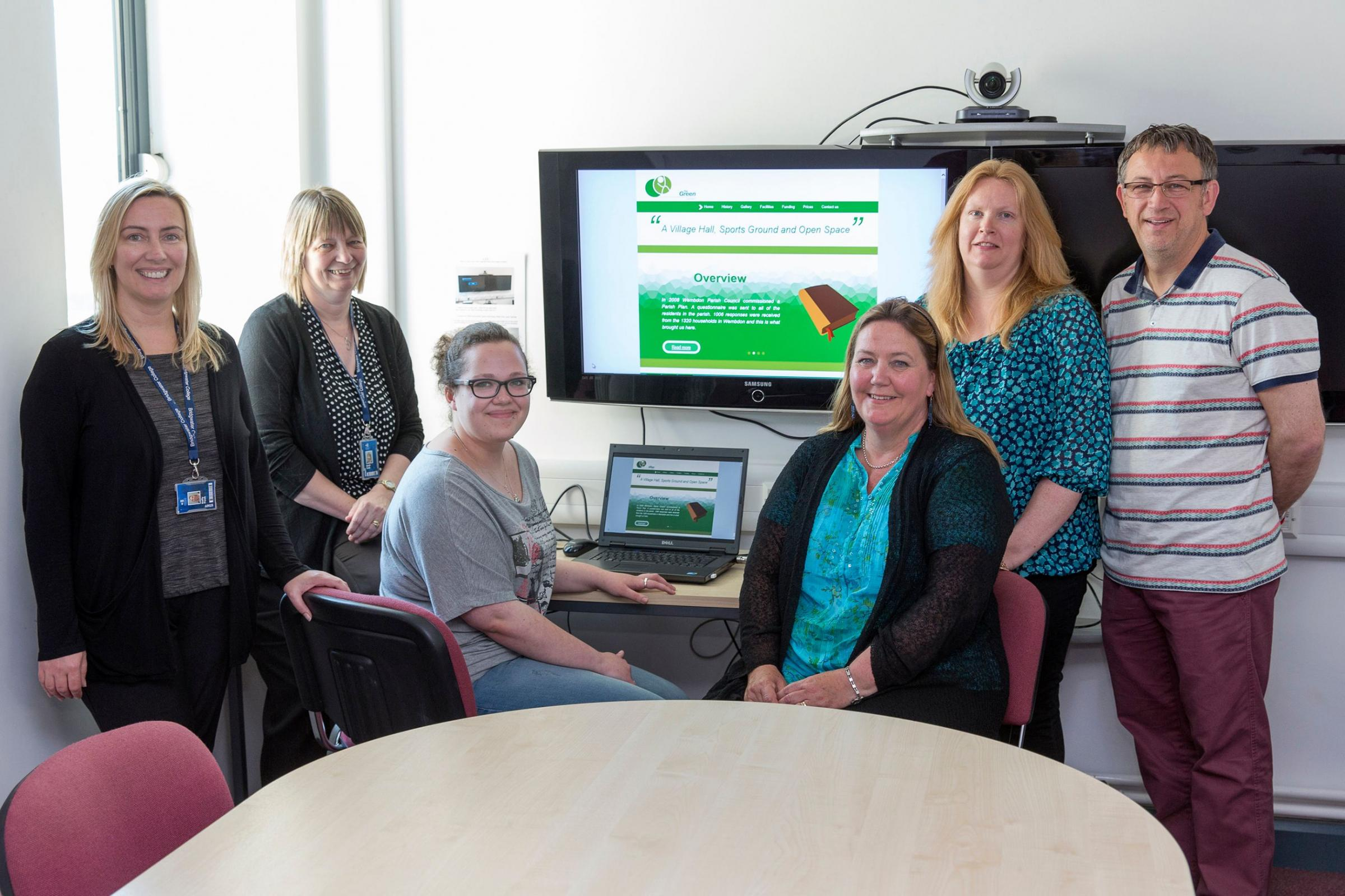 IEVA with members of Bridgwater College staff and committee members in front of the website design.