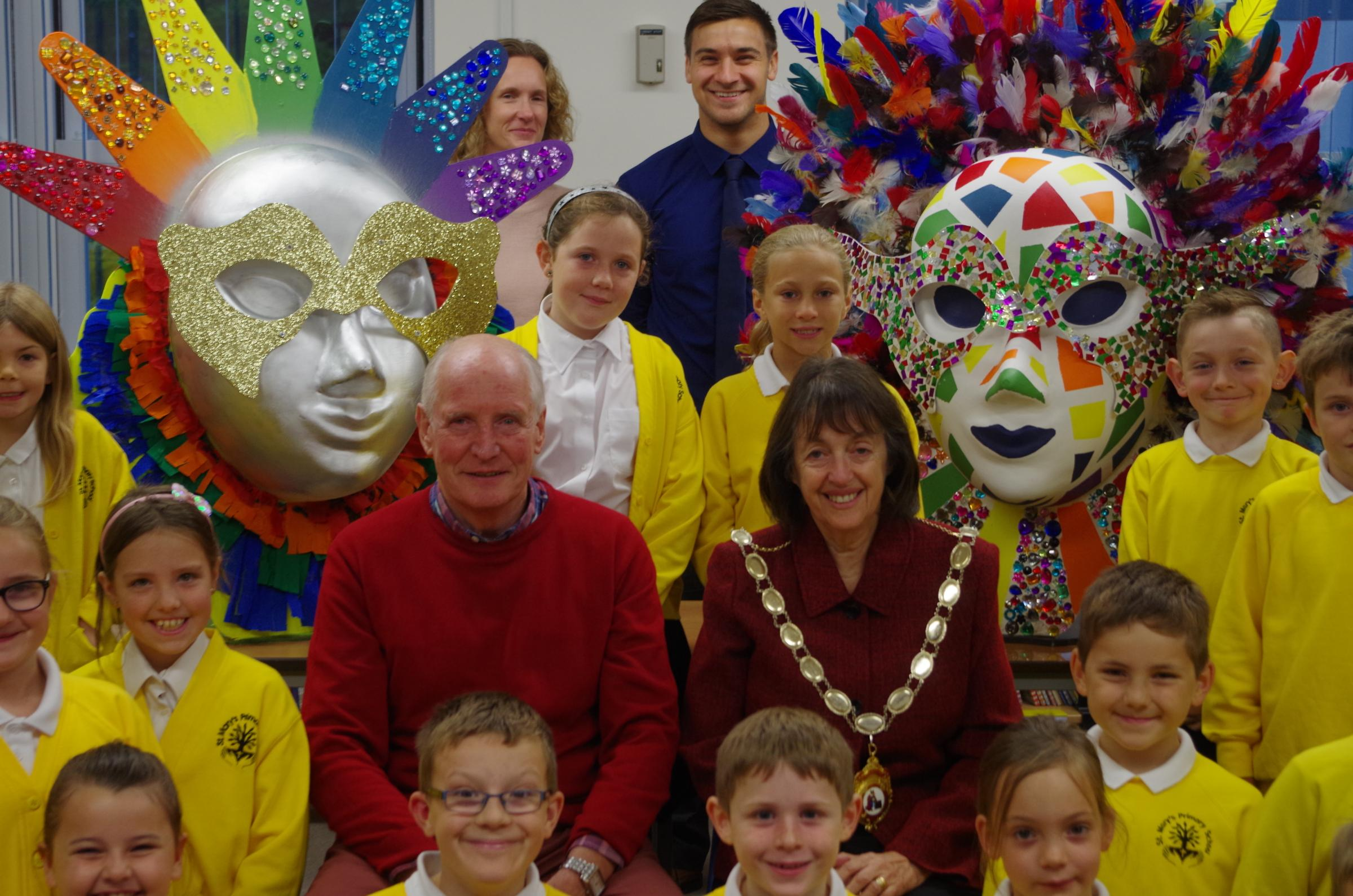 Pictured with the children of St Mary's Primary School in Bridgwater and their carnival masks is the President of the Carnival Rita Jones and committee member Chris Hocking