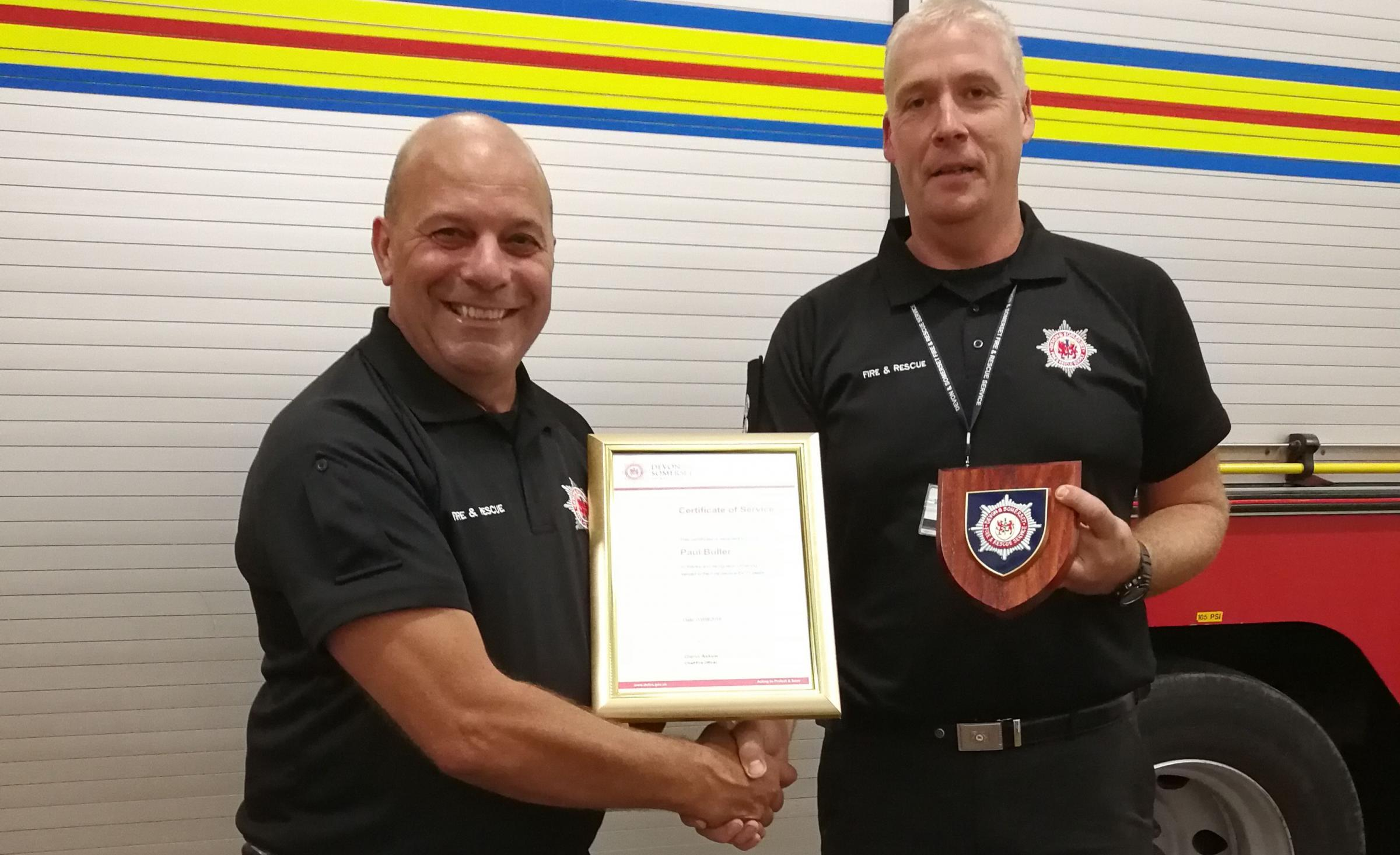 AWARD: Nether Stowey watch manager Nick Rich presents Paul Buller with his certificate of service and a commemorative plaque after 31 years as on-call firefighter